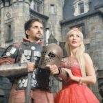 51849638 - medieval knight with his beloved lady. ancient castle on the background.